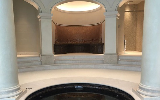 Steam room with circular seating area and mosaic design