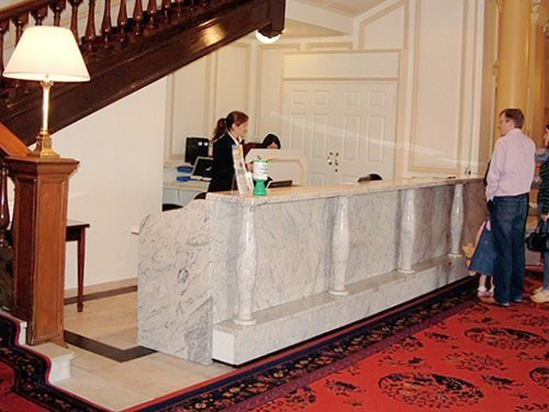 Ivory white granite hotel reception desk with pillars