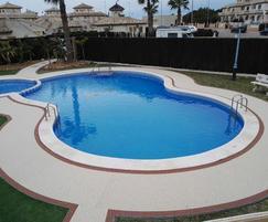 Addaset slip resistant surfacing surrounding a pool