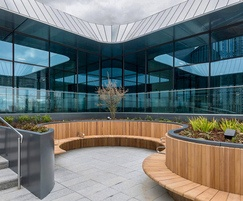 Sinuous iroko seating on roof garden