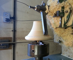 Hand turning the bell top finial