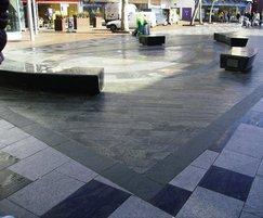 Curved, polished stone seat in pedestrian area