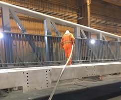 Paint system being applied to bridge