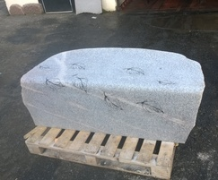 Curved top glacial boulder bench with carving