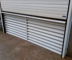 Fixed ventilation louvre under a roller shutter door