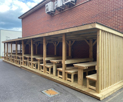 Outdoor shelter with seating and tables for school